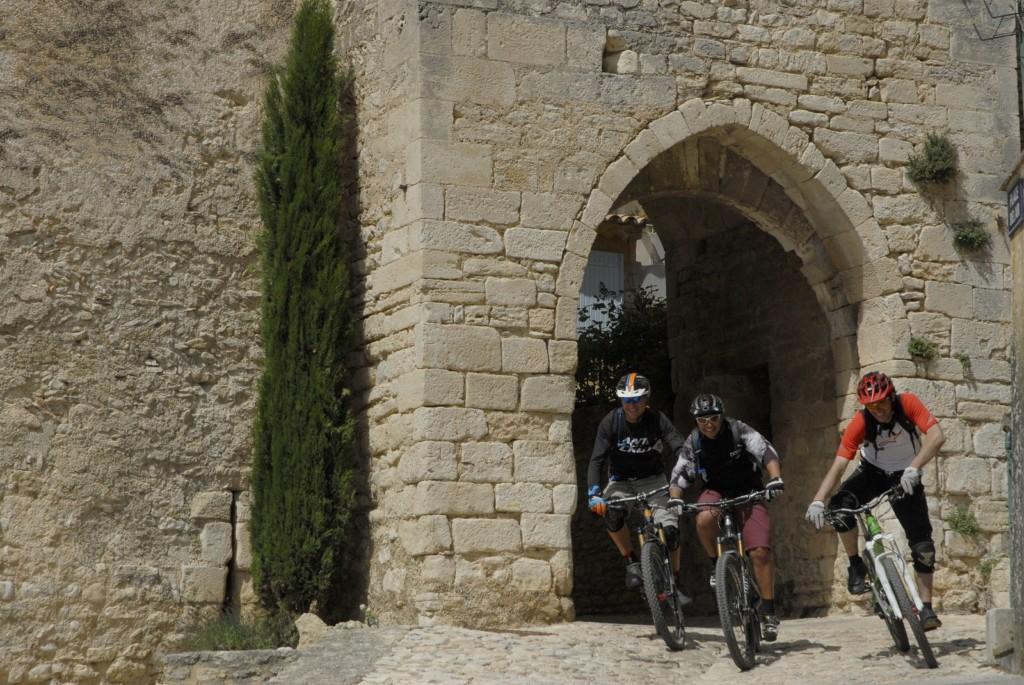 3 personnages à VTT sortant d'une rue de Saint-Saturnin-lès-Apt